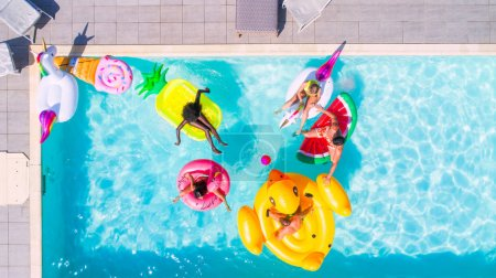 Photo for Happy people partying in an exclusive swimming pool with animal and fruit shapes mats, view from above - Royalty Free Image