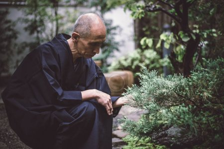 Senior japanese man taking care of his garden