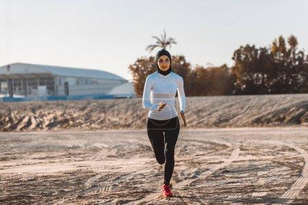 Photo pour Arabe femme courir en plein air et porter hijab - image libre de droit