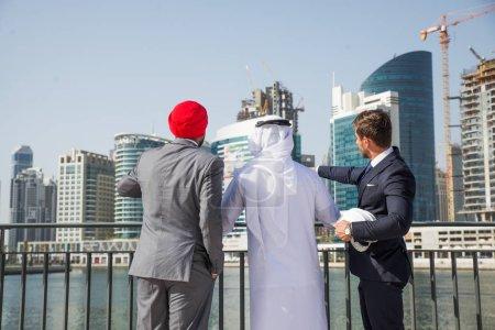 """Photo pour Réunion de l """"équipe d'affaires multiethnique à l'extérieur - Trois hommes d'affaires parlent d'affaires lors d'une réunion formelle - image libre de droit"""