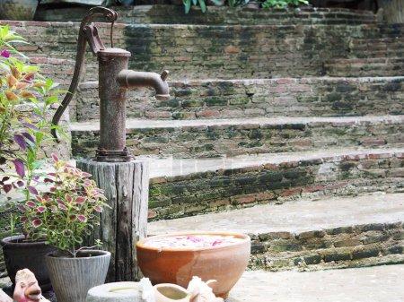 Photo pour Pompe à eau rouillée vintage dans le jardin - image libre de droit