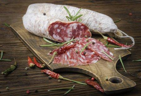 Photo pour Salami italien avec du poivre et de romarin sur une planche de bois - image libre de droit