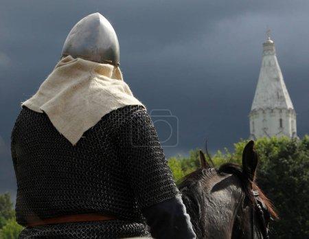 Reiter in Rüstung vor dem Hintergrund von Kirche und stürmischem Himmel