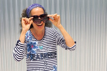 Laughing mature woman wearing two pairs of sunglasses. Silver grey corrugated panel in the background.