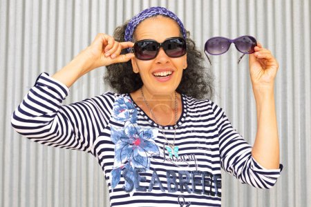 A smiling mature woman wearing sunglasses is holding another pair near her face. Silver corrugated panel in the background.