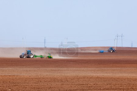 spring landscape tractor plowing endless field against the blue sky and the power line on the horizon