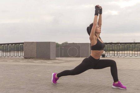 Photo pour Brunette slim adulte sexy fit femme caucasienne sportive en vêtements de sport sur une ville européenne rues le matin faire des exercices (séance d'entraînement), étirer ses jambes et les fesses. Espace de copie - image libre de droit