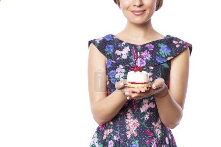 Photo pour Brunette jolie belle femme caucasienne en robe de fête bleue soufflant bougie sur un cupcake de fête d'anniversaire. Fond blanc isolé - image libre de droit