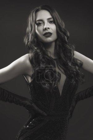 Photo pour Glamour caucasienne brune en soirée en robe noire sur un fond neutre. Elle pose avec sensualité. Humeur mode rétro - image libre de droit