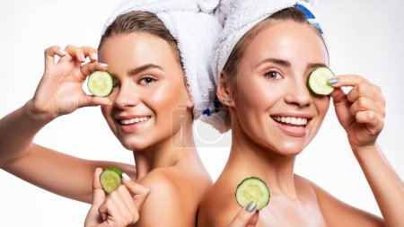 Photo pour Deux jolies femmes souriantes appliquent des tranches de concombre sur leur visage avec des serviettes sur la tête. Peau fraîche propre et naturelle. Fond studio blanc. - image libre de droit