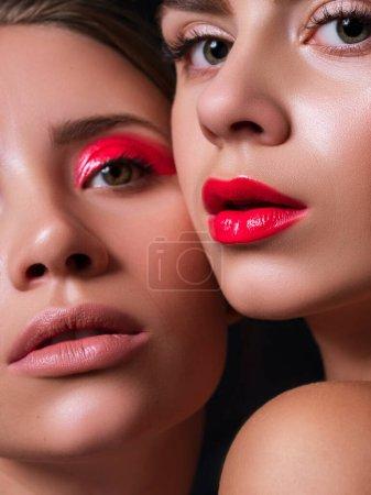 Photo pour Deux femmes ensemble proches l'une de l'autre avec des lèvres rouges et des yeux. Fermer concept de cosmétiques de beauté créatifs. Peau fraîche sans défaut. Portrat sur fond sombre. - image libre de droit