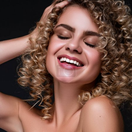 Photo for Cute cheerful woman close up portrait with afro curly hairstyle on a black background. Fresh, flawless skin. - Royalty Free Image