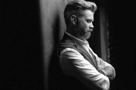 Photo pour Portrait d'un bel homme souriant à la barbe, vêtu d'une chemise blanche et d'un gilet noir, posant latéralement en studio sur fond gris foncé en noir et blanc - image libre de droit
