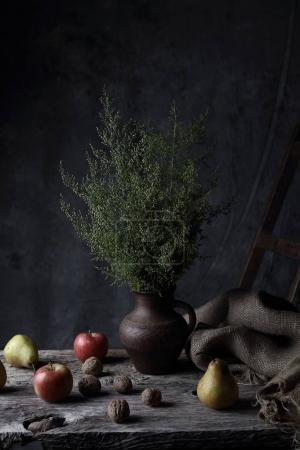 schönes Stillleben mit Walnüssen, Birnen, Äpfeln und Krug mit grünen Pflanzen darin, auf Holztisch im dunklen Atelier