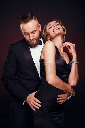 Photo for Luxurious, elegant and happy couple: handsome bearded man in tuxedo with amazing woman with blonde updo hair, wearing silky black dress and chic jewelry, posing in dark studio - Royalty Free Image