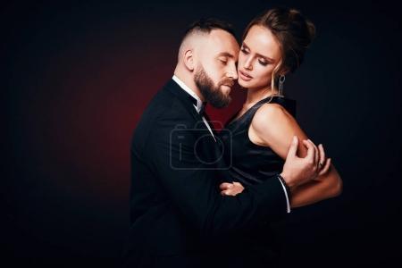 Photo pour Couple sexy, élégant: beau barbu homme en smoking avec une femme étonnante avec des cheveux blonds, portant robe noire soyeuse et bijoux chic, qui pose en studio sombre - image libre de droit