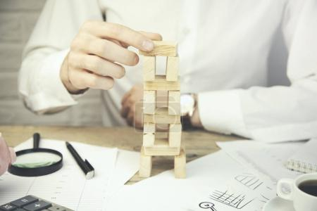 Businessman hand wooden cubes