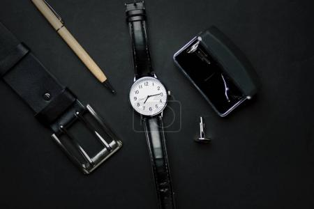 Men's accessories with wallet, belt,pen, and watch on black background