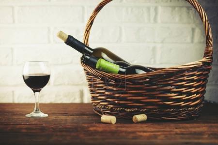 Wine bottles in basket on wooden table