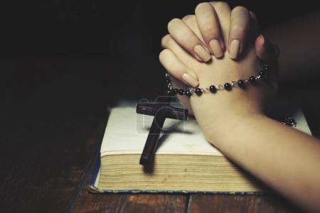 Photo for Praying woman holds  cross. Bible in background. - Royalty Free Image