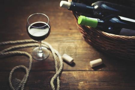 wine glass and   bottols on basket