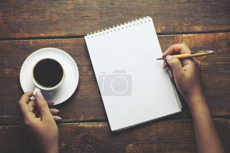 Photo pour Femme stylo à main et café dans ofice - image libre de droit