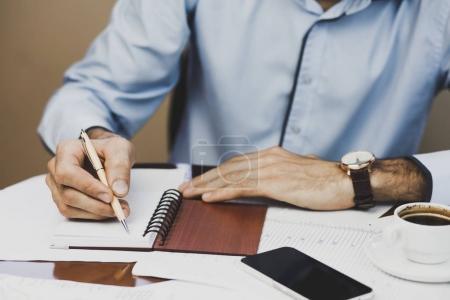 Photo pour Homme écrivant dans un cahier avec stylo, gros plan - image libre de droit