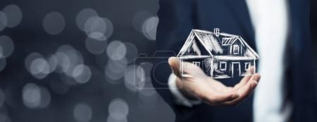 Photo for Real estate offer. Businessman holding   model of the house - Royalty Free Image