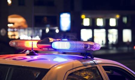 Photo pour Des clignotants bleus sur la voiture de police. Lumières de ville sur le fond . - image libre de droit