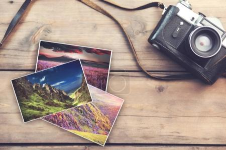 Photo for Camera and photos on wooden table, close up - Royalty Free Image