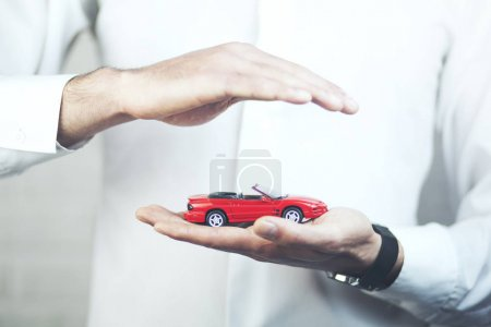 toy car in the hands of a businessman, close up