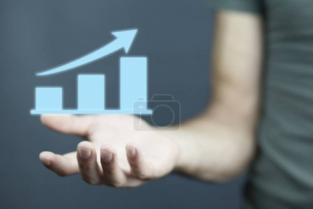 Photo for Hand holding a rising arrow, representing business growth - Royalty Free Image