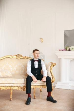 Groom sitting on the sofa waiting for the bride on his wedding day. at wedding tuxedo smiling and waiting for bride.Elegant man in black costume and bow-tie.