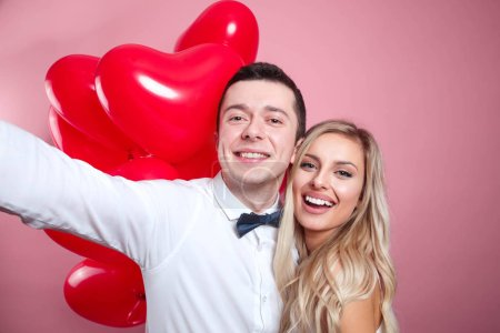 Photo for Beautiful young romantic couple taking selfie on mobile phone and standing with red balloons on pink background - Royalty Free Image