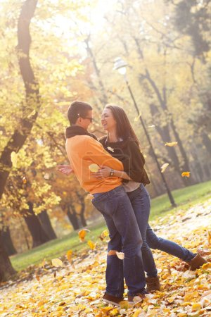 Photo for Lovely couple spending time in autumn park, man and woman smiling while hugging - Royalty Free Image