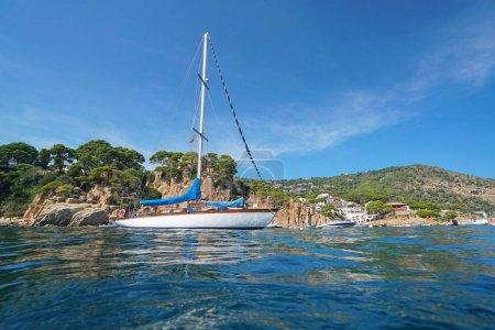 Spain a sailboat near rocky coastline Costa Brava