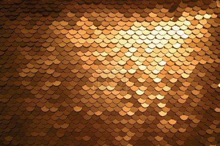 Pailletten Nahaufnahme Makro. abstrakter Hintergrund mit goldenen Pailletten auf dem Stoff. Texturskalen von runden Pailletten mit Farbübergang.