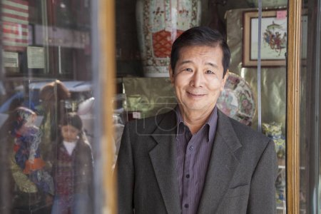 Asian man in front of store