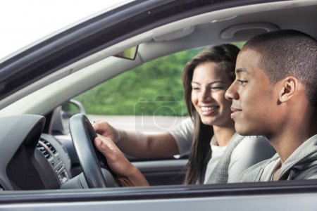 Happy teenagers driving car