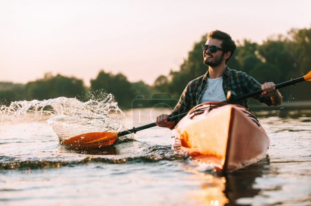 Photo for Young man kayaking on river, sport and sunset concept - Royalty Free Image