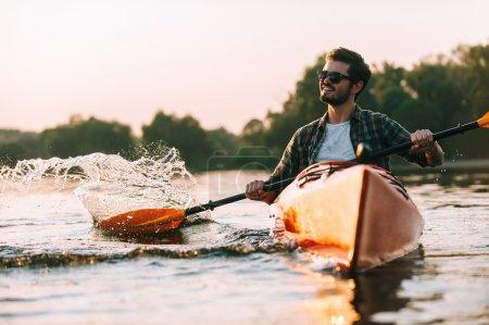 Photo pour Jeune homme en kayak sur la rivière, sport et le concept du coucher du soleil - image libre de droit