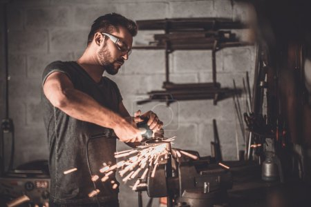 Photo for Handsome welder in garage grinding with sparks in repair shop - Royalty Free Image