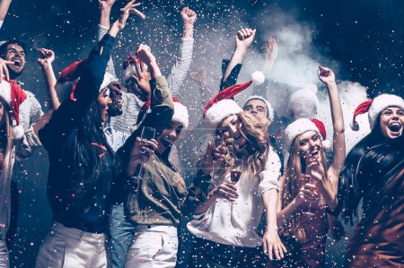 Photo for Beautiful young people dancing in Santa hats throwing colorful confetti and looking happy, new year concept - Royalty Free Image