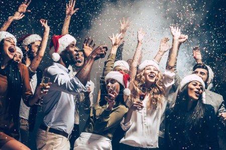 Photo pour Beaux jeunes gens danser en jetant des confettis colorés et l'air heureux, notion de nouvel an, chapeaux de Santa - image libre de droit