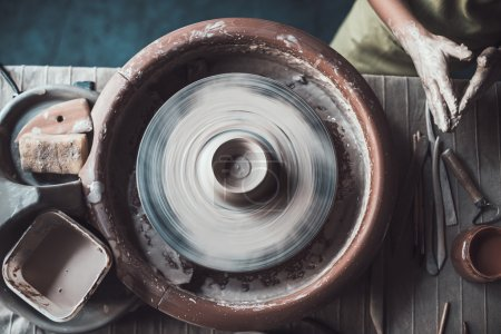 man making pot on pottery wheel