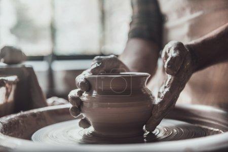 man making ceramic pot