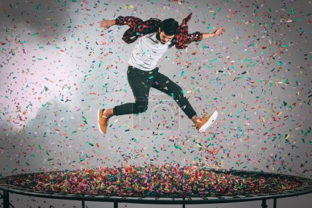 Photo for Happy man jumping on trampoline with confetti around them, studio shot - Royalty Free Image