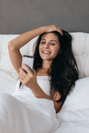 Attractive woman holding smartphone in bed
