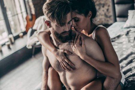 Photo pour Couple d'amoureux à la maison après avoir journée de farniente, hipster beau avec une belle jeune fille gardant les bras autour de lui - image libre de droit