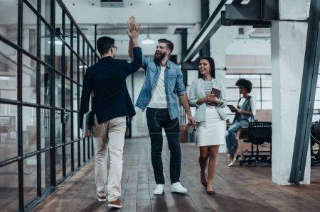 Photo pour Joyeux jeunes gens d'affaires donnant haute cinq dans le bureau loft moderne - image libre de droit